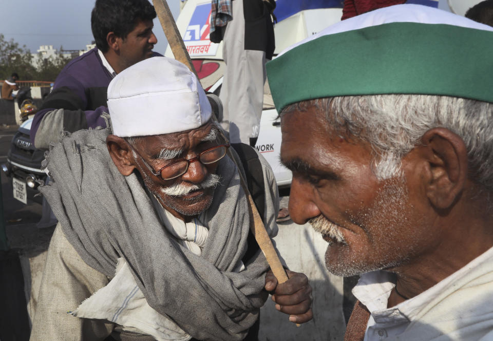 Elderly farmers talk on a heavily barricaded road along one of the three main protest sites outside New Delhi's border to thwart the growing farmers' protest on the edges of the capital, at Delhi-Uttar Pradesh border, in New Delhi, India, Friday, Feb. 5, 2021. India's agriculture minister on Friday defended the new agriculture reform laws in Parliament, dampening hopes of any quick settlement with tens of thousands of protesting farmers demanding their repeal by blocking three highways connecting New Delhi to northern India for over two months now. (AP Photo/Manish Swarup)