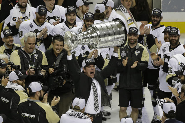 FILE - In this June 12, 2016, file photo, Pittsburgh Penguins head coach Mike Sullivan raises the Stanley Cup after Game 6 of the NHL hockey Stanley Cup Finals against the San Jose Sharks in San Jose, Calif. Sullivan is sticking around to see if he can get the Penguins back to the Stanley Cup. The club announced Friday, July 5, 2019, that it has signed Sullivan who guided the Penguins to championships in 2016 and 2017 to a four-contract extension that runs through the 2023-24 season. (AP Photo/Eric Risberg, File)