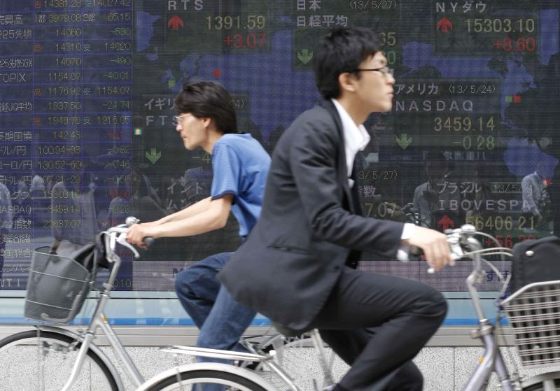 Cyclists pass by an electronic stock board of a securities firm in Tokyo Monday, May 27, 2013. The Nikkei 225 closed down 469.80 points, or 3.22 percent at 14,142.65 Monday after the yen reversed some of its recent fall against the U.S. dollar. Stocks elsewhere in Asia were mixed as investors tried to sort out conflicting indicators about the health of the global economy. (AP Photo/Koji Sasahara)