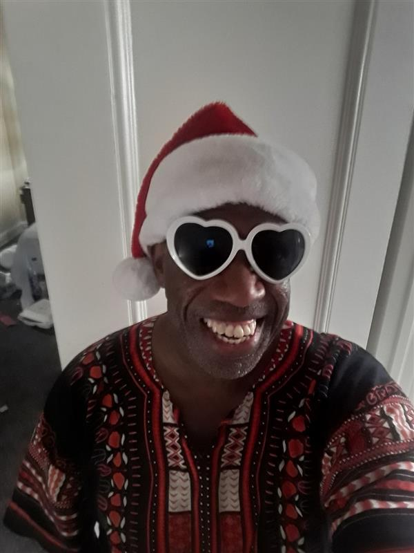 Tyree Leslie, 51, takes a Christmas selfie in his hotel room where he has been riding out the pandemic. Leslie, a teacher who works with students receiving special education services, has been experiencing homelessness about a year after losing his job and safety net.