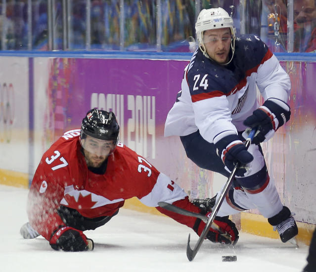 Canada forward Patrice Bergeron USA forward Ryan Callahan vie for the puck during the first period of a men's semifinal ice hockey game at the 2014 Winter Olympics, Friday, Feb. 21, 2014, in Sochi, Russia. (AP Photo/Julio Cortez)