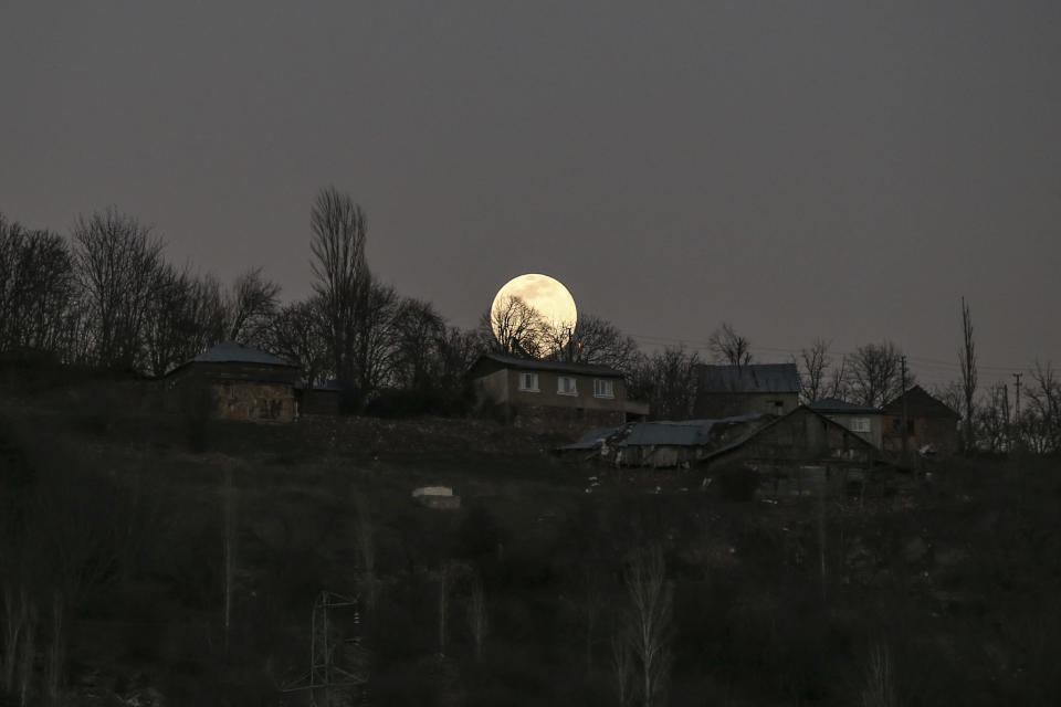 A full moon rises over the isolated village of Gumuslu in the district of Sivas, central Turkey, Friday, Feb. 26, 2021. Vaccination teams in Turkey have been reaching isolated mountain villages in Turkey's central Sivas province as the government aims to inoculate 60% of the country's population against the coronavirus over the next three months. (AP Photo/Emrah Gurel)