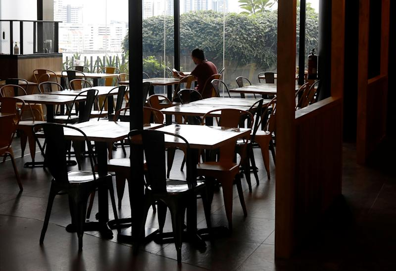 A man sits in an empty restaurant, during the coronavirus disease (COVID-19) outbreak, in Singapore, August 12, 2020. REUTERS/Edgar Su