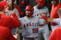 Los Angeles Angels' Jack Mayfield (59) is congratulated in the dugout by teammates after scoring on a wild pitch in the third inning of a baseball game against the Texas Rangers, Thursday, Aug. 5, 2021, in Arlington, Texas. (AP Photo/Brandon Wade)