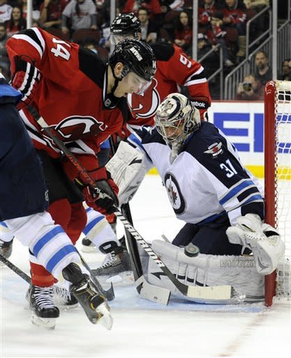 New Jersey Devils' Adam Henrique, left, attempts to score past Winnipeg Jets goaltender Ondrej Pavelec, of the Czech Republic, during the second period of an NHL hockey game Sunday, Feb. 24, 2013, in Newark, N.J. (AP Photo/Bill Kostroun)