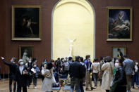 People stroll in the Louvre museum with the marble hellenic sculpture The Winged Victory of Samothrace, in the background, Wednesday, May, 19, 2021 in Paris. Museums must restrict entries so there is 8 square meters of space (86 square feet) per visitor. Café and restaurant terraces are reopening Wednesday after a shutdown of more than six months deprived people of what feels like the essence of life — sipping coffee and wine with friends outdoors — to save lives during the coronavirus pandemic. (AP Photo/Thibault Camus)