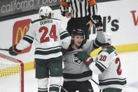 Los Angeles Kings right wing Adrian Kempe, center, celebrates after a goal by Gabriel Vilardi while Minnesota Wild defensemen Mathew Dumba, left, and Ryan Suter look on during the first period of an NHL hockey game in Los Angeles, Saturday, Jan. 16, 2021. (AP Photo/Kelvin Kuo)