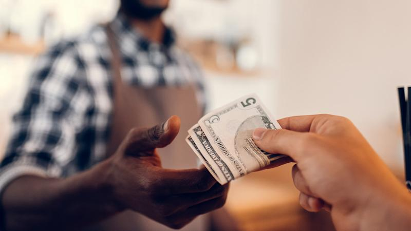 selective focus of african american barista taking cash payment on bar counter in cafe.