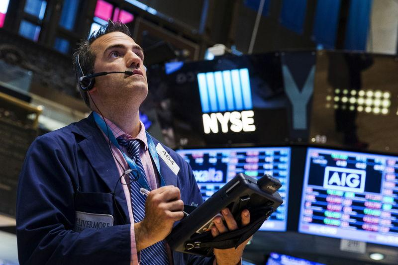 A trader looks at boards shortly after the closing bell on a day that saw a several hour long stoppage on the floor of the New York Stock Exchange
