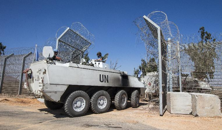 Members of the United Nations Disengagement Observer Force cross with their armoured vehicles from the Israeli-annexed Golan Heights into the Syrian-controlled territory, on August 28, 2014