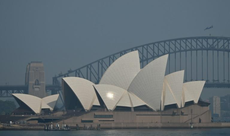 The Sydney Opera House and Harbour Bridge are seen through a smokey haze blanketing the city