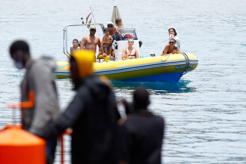 A group of tourists on a boat observes several migrants waiting to disembark from a Spanish coast guard vessel, in the port of Arguineguin