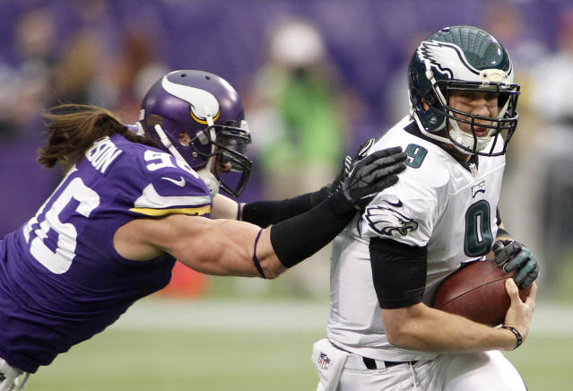 Philadelphia Eagles quarterback Nick Foles, right, runs from Minnesota Vikings defensive end Brian Robison during the first half of an NFL football game, Sunday, Dec. 15, 2013, in Minneapolis. (AP Photo/Andy King)