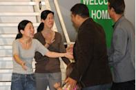 <p>Journalist Euna Lee (left) embraces her husband Michael Saldate (far right) and daughter Hana, while fellow journalist Laura Ling (second from left) greets husband Iain Clayton after being released from North Korea. Following talks in Pyongyang with former U.S. president Bill Clinton, North Korean leader Kim Jong Il pardoned Lee and Ling, who had been sentenced to hard labor for entering the country illegally. </p>