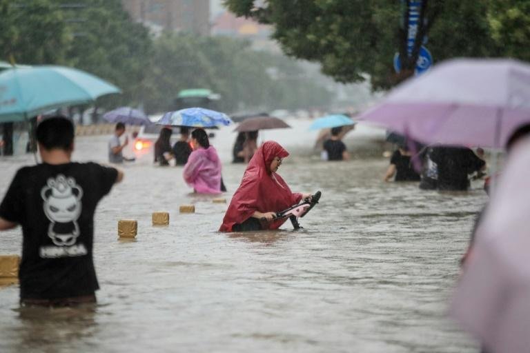 As heavy rain pounded central China, floodwaters trapped people in a subway