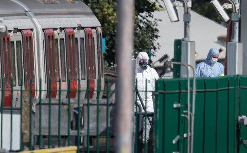 Forensics officers, one is a gas mask (L) can be seen next to the evacuated tube train - Credit: Peter Macdiarmid/LNP