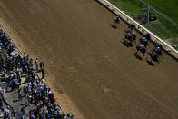 Fans watch as horses run a race before the 147th running of the Kentucky Derby at Churchill Downs, Saturday, May 1, 2021, in Louisville, Ky. (AP Photo/Brynn Anderson)