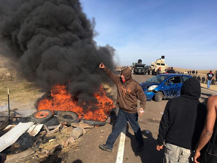 <p>Demonstrators stand next to burning tires as armed soldiers and law enforcement officers assemble on Thursday, Oct. 27, 2016, to force Dakota Access pipeline protesters off private land where they had camped to block construction. The pipeline is to carry oil from western North Dakota through South Dakota and Iowa to an existing pipeline in Patoka, Ill. (Photo: Mike McCleary/The Bismarck Tribune via AP) </p>