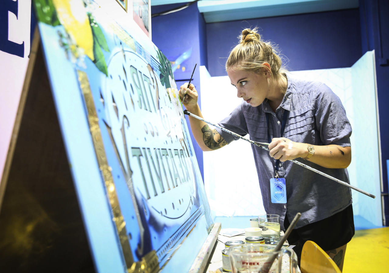 Artist Alex May Hughes prepares for the launch of Bombay Sapphire 'Canvas', a pop-up creative arts space in London, Tuesday July 17, 2018. (Matt Alexander/PA via AP)