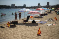 Spanish flags being used as social distancing signage stick out from the sand in Palma de Mallorca, Spain, Sunday, July 26, 2020. Britain has put Spain back on its unsafe list and announced Saturday that travelers arriving in the U.K. from Spain must now quarantine for 14 days. The move by the UK taken without forewarning has caught travelers off guard. (AP Photo/Joan Mateu)