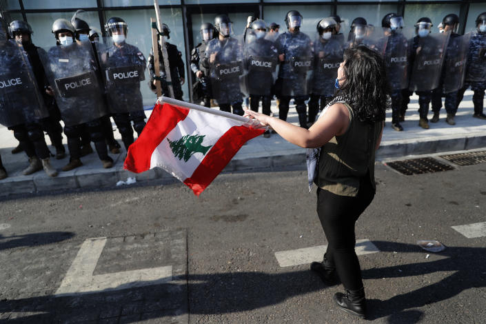 An anti-government protester holds a Lebanese flag in front the riot police during a protest against the deepening financial crisis, in Beirut, Lebanon, Tuesday, April 28, 2020. Hundreds of protesters in Lebanon's northern city of Tripoli set fire Tuesday to two banks and hurled stones at soldiers, who responded with tear gas and batons in renewed clashes triggered by an economic crisis spiraling out of control amid a weeks-long virus lockdown. (AP Photo/Hussein Malla)
