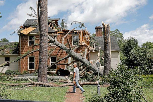 PHOTO: A man walks past a damaged house with a chainsaw in the Riverview neighborhood of Suffolk, Va., after Hurricane Isaias moved through the region Aug. 4, 2020. (Jonathon Gruenke/The Daily Press via AP)