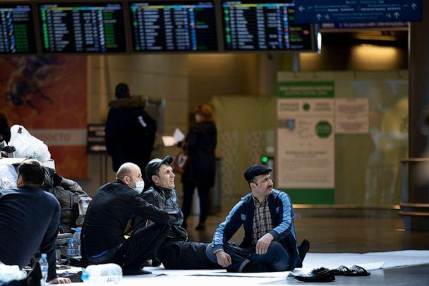 PHOTO: Citizens of Tajikistan rest on the floor waiting for a plane to return in their home country at the Vnukovo International Airport, southwest of Moscow, Russia, on March 24, 2020. (Alexander Zemlianichenko/AP)