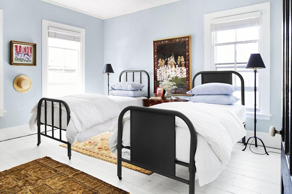 """<p>For a pretty and relaxing bedroom, you can't top a soft pale blue. It's also a color that works well for lots of different styles, from coastal to traditional. Here, the bedroom takes a modern turn thanks to its black accent color. The pair of mismatched black twin beds (they work together because the headboards are the same shape and height) and black shaded floor lamps ground the room and add contrast to the airy wall color.</p><p><strong> Get the Look: </strong><br>Wall Paint Color: <a href=""""https://store.benjaminmoore.com/storefront/index.ep"""" rel=""""nofollow noopener"""" target=""""_blank"""" data-ylk=""""slk:Woodlawn Blue by Benjamin Moore"""" class=""""link rapid-noclick-resp"""">Woodlawn Blue by Benjamin Moore</a></p>"""