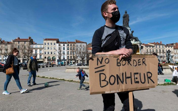 """An anti-deportation protester in Le Puy-en-Velay, central France, last month with a placard that reads: """"No border = happiness"""" - GETTY IMAGES"""