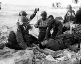 FILE - In this June 1944, file photo, U.S. Army medical personnel administer a transfusion to a wounded comrade, who survived when his landing craft went down off the coast of Normandy, France, in the early days of the Allied landing operations. A dwindling number of D-Day veterans will be on hand in Normandy in June 2019, when international leaders gather to honor them on the invasion's 75th anniversary. (U.S. Army Signal Corps via AP, File)