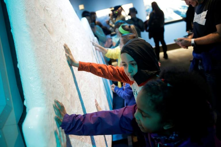 "Students on a field trip place their hands on a ice glacier replica during the ""Extreme Ice"" exhibit at the Museum of Science and Industry in Chicago, Illinois"