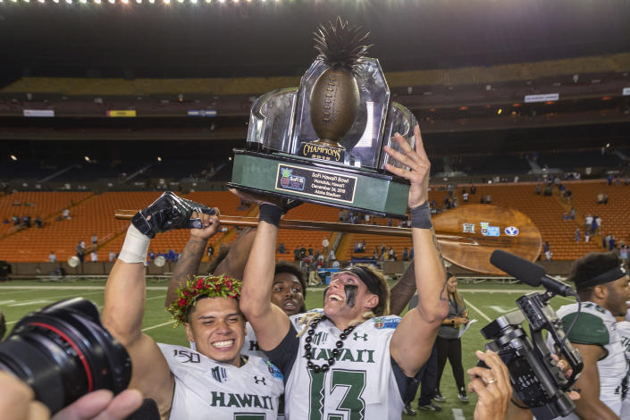 Hawaii quarterback Cole McDonald (13) holds up the Hawaii Bowl trophy, next to wide receiver Jason-Matthew Sharsh, left, after the team's 38-34 win over BYU in the NCAA college football game Tuesday, Dec. 24, 2019, in Honolulu. (AP Photo/Eugene Tanner)