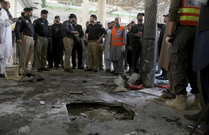 Police officers examine the site of bomb explosion in an Islamic seminary in Peshawar, Pakistan, Tuesday, Oct. 27, 2020. A powerful bomb blast ripped through an Islamic seminary on the outskirts of the northwest Pakistani city of Peshawar on Tuesday morning, killing some students and wounding dozens others, police and a hospital spokesman said. (AP Photo/Muhammad Sajjad)