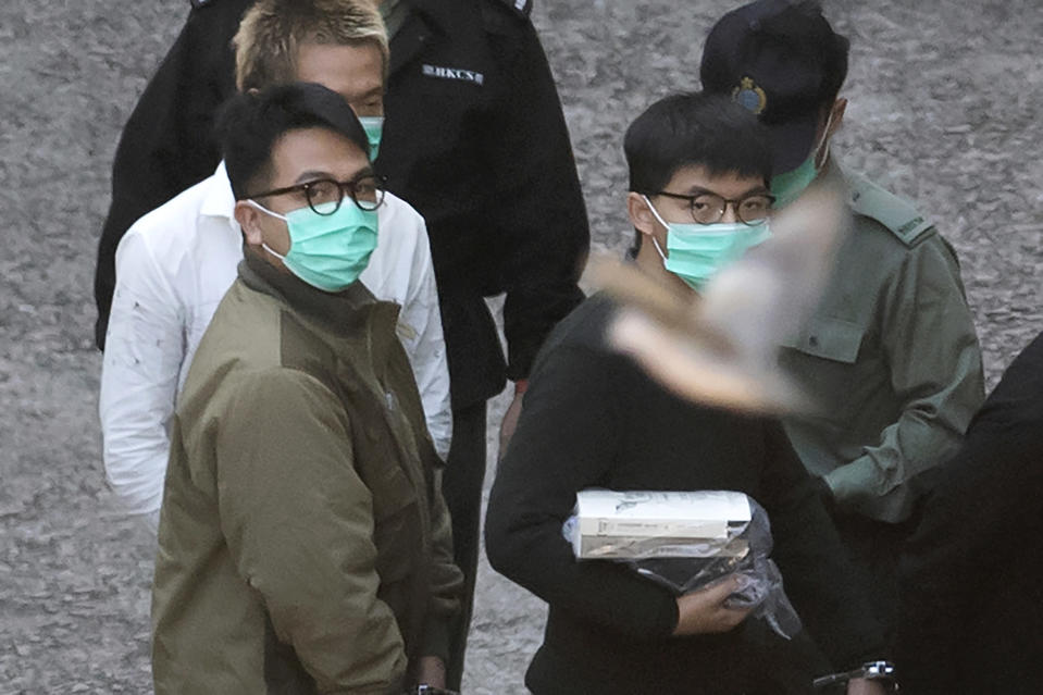A bird flies as Hong Kong activists Joshua Wong, right, and Ivan Lam, left, are escorted by Correctional Services officers to get on a prison van before appearing in a court, in Hong Kong, Wednesday, Dec. 2, 2020. Prominent Hong Kong pro-democracy activist Wong and two other activists, Lam and Agnes Chow, were taken into custody after they pleaded guilty to charges related to a demonstration outside police headquarters during anti-government protests last year. (AP Photo/Kin Cheung)