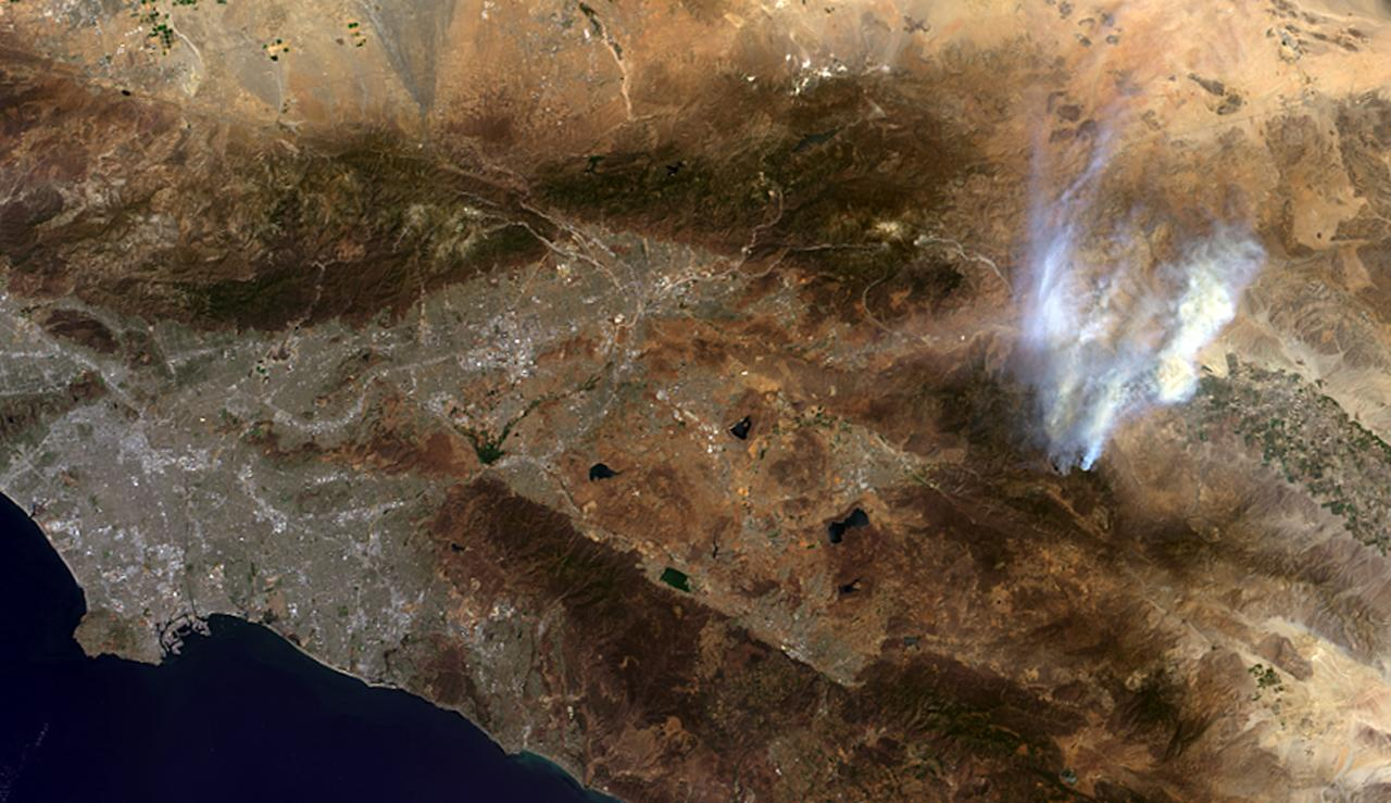 This image provided by NASA shows the agency's Terra spacecraft photo showing smoke from a wildfire near Idyllwild, Calif., right, and the Los Angeles area, left. The blaze in the San Jacinto Mountains has expanded to roughly 39 square miles and was 15 percent contained Friday July 19, 2013. (AP Photo/NASA)