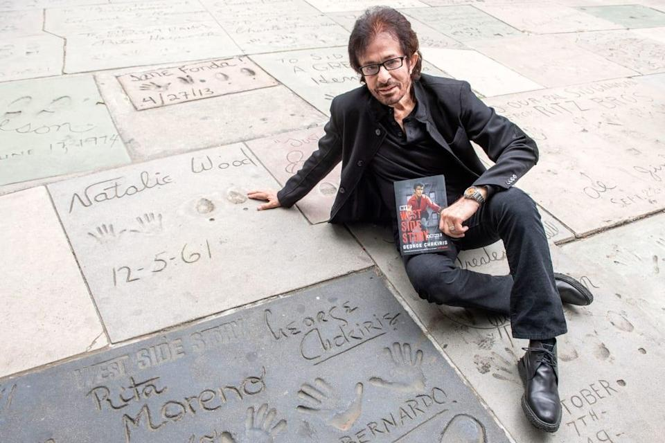 """<div class=""""inline-image__caption""""><p>George Chakiris poses with his book next to his handprints during the ceremony unveiling the new plaque honoring all the 100+ Oscar winners who got their handprint-footprints at the TCL Chinese Theater, April 21, 2021, in Hollywood, California.</p></div> <div class=""""inline-image__credit"""">Valerie Macon/AFP/Getty</div>"""