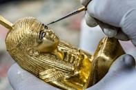 A technician paints a replica of an ancient Egyptian statue at the Konouz (Treasures) factory in Cairo