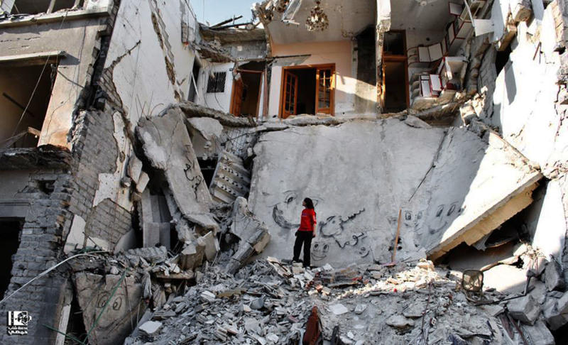In this citizen journalism image provided by Lens Young Homsi, which has been authenticated based on its contents and other AP reporting, shows a Syrian standing in the rubble of a destroyed buildings from Syrian forces shelling, in the al-Hamidiyyeh neighborhood of Homs province, Syria, Thursday, June 27, 2013. (AP Photo/Lens Young Homsi)