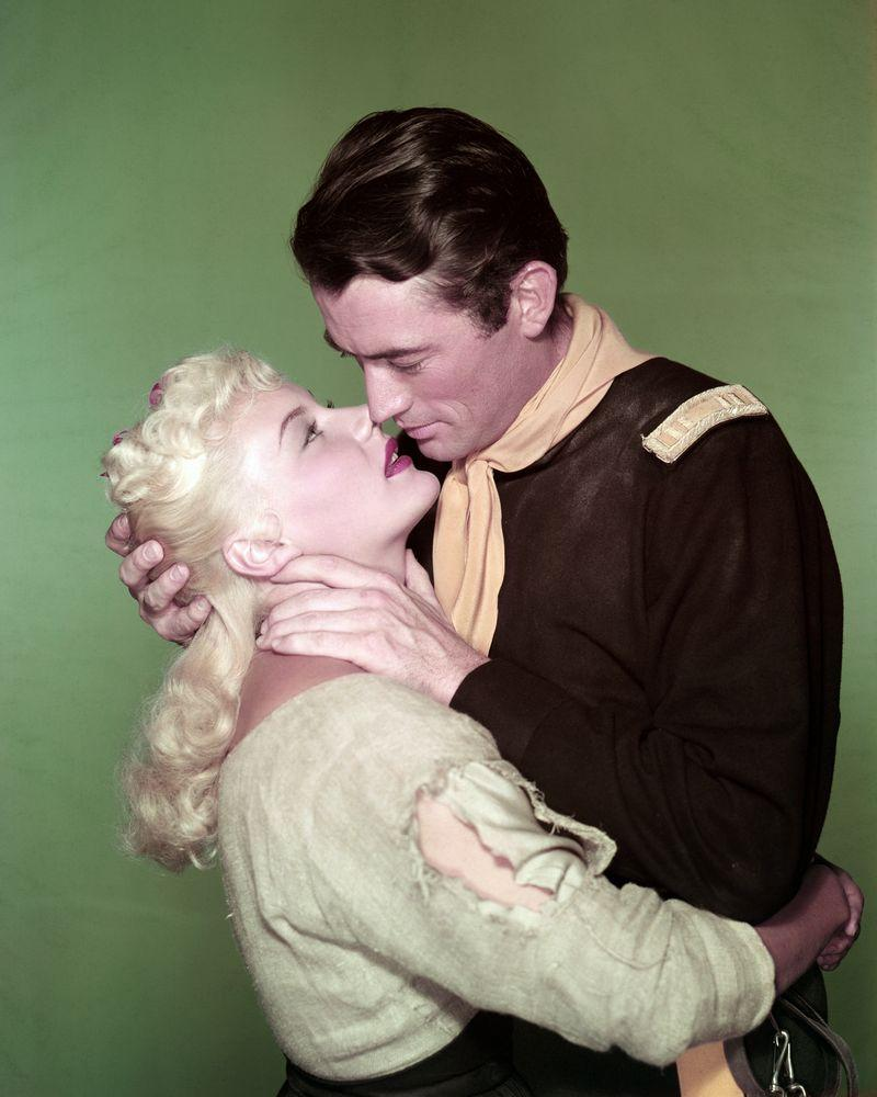 American actors Gregory Peck (1916 - 2003) and Barbara Payton (1927 - 1967) kiss in a publicity still for 'Only the Valiant', directed by Gordon Douglas, 1951.