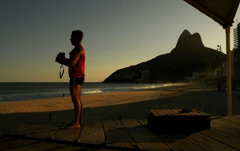 With Rio's beaches closed to all but surfers, a lifeguard looks out over an empty Ipanema beach on April 28, 2020