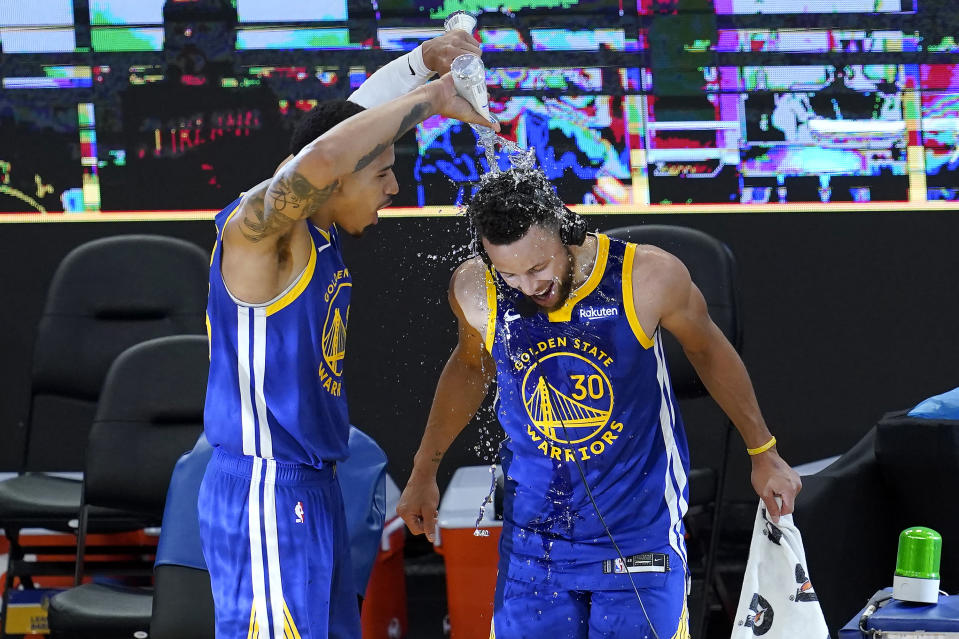 Golden State Warriors forward Juan Toscano-Anderson, left, pours water onto guard Stephen Curry (30) after the Warriors defeated the Denver Nuggets in an NBA basketball game in San Francisco, Monday, April 12, 2021. (AP Photo/Jeff Chiu)