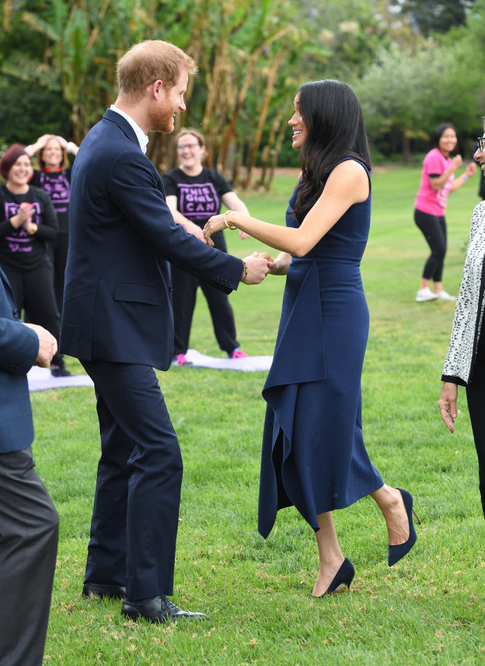 <p>With the help of her hubby Harry, Meghan took to the grass in a Dion Lee navy blue dress costing $1290 and her Manolo Blahnik BB pumps in navy suede. Photo: Getty </p>
