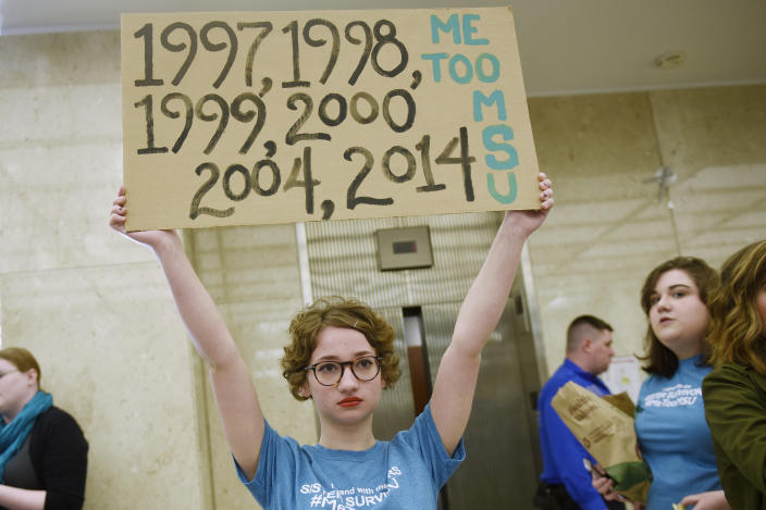FILE - In this April 13, 2018 file photo, Morgan McCaul, 18, a survivor of Larry Nassar abuse, holds a sign showing the years that Larry Nassar was reported to Michigan State University as trustees arrive for a university board meeting. The government's $4.5 million fine against Michigan State University in the Nassar sexual assault scandal is unprecedented. The U.S. Education Department has extraordinary leverage over schools that participate in federal student aid programs. (Clarence Tabb Jr./Detroit News via AP, File)