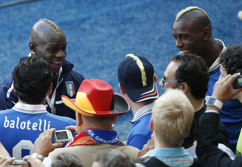 Italy's Mario Balotelli, left, chats with his brother Enoch, right, and other fans prior to the Euro 2012 soccer championship final between Spain and Italy in Kiev, Ukraine, Sunday, July 1, 2012. (AP Photo/Darko Vojinovic)