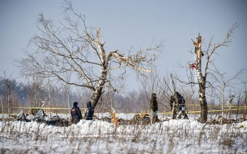 Emergency workers examine debris from the An-148 plane that crashed on Sunday, killing all 71 on board. - Credit: Vasily Maximov/AFP/Getty Images