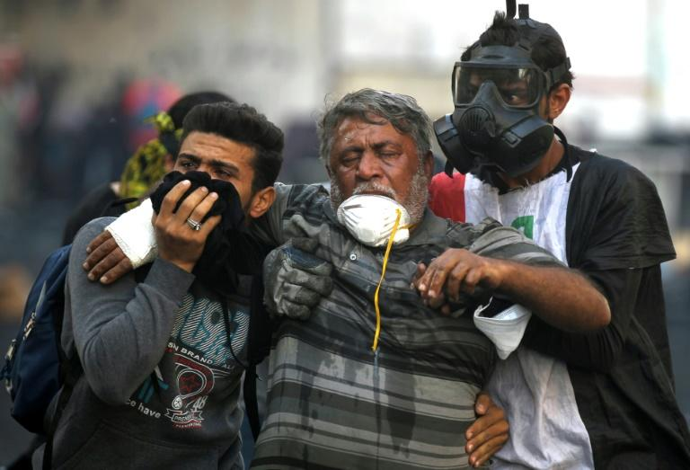 Iraqi volunteers help a protester affected by tear gas fired by security forces amid clashes at Baghdad's Khallani Square (AFP Photo/AHMAD AL-RUBAYE)
