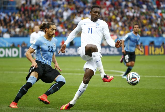 England's Danny Welbeck (C) fights for the ball with Uruguay's Martin Caceres during their 2014 World Cup Group D soccer match at the Corinthians arena in Sao Paulo June 19, 2014. REUTERS/Tony Gentile (BRAZIL - Tags: SOCCER SPORT WORLD CUP)