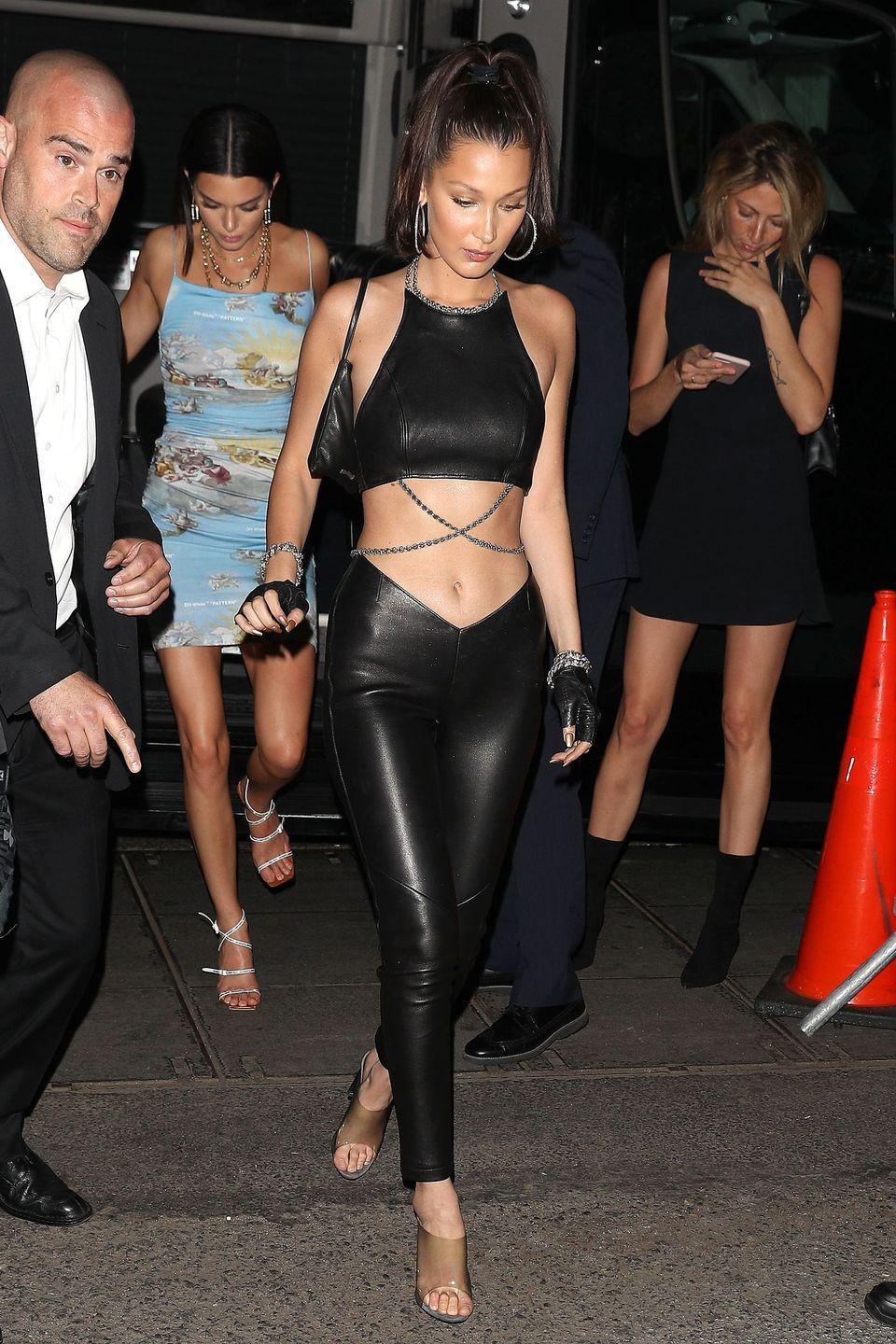 <p>in a black leather chain-linked crop top with matching pants, PVC heels, and fingerless leather gloves heading out of New York's Mercer hotel.</p>