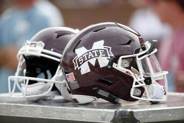 FILE - This is an April 21, 2018, file photo showing Mississippi State football helmets on the sideline during the second half of Mississippi State's Maroon and White spring NCAA college football game, in Starkville, Miss. Mississippi State has received three years probation from the NCAA after an investigation determined a part-time student tutor completed coursework for 10 football players and one mens basketball player in an online class. (AP Photo/Rogelio V. Solis, File)