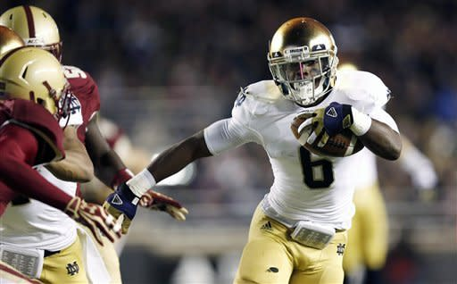 Notre Dame running back Theo Riddick breaks out past Boston College defenders during the first half of an NCAA college football game in Boston on Saturday, Nov. 10, 2012. (AP Photo/Winslow Townson)
